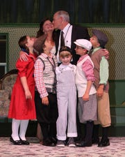 Mr. and Mrs. Gilbreth (Peggy Whelan and Lawrence Gaughan) are besieged by some of their children, but they don't seem to mind.