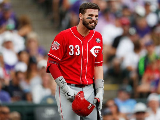 Cincinnati Reds' Jesse Winker reacts after hurting himself while swinging at a pitch from Colorado Rockies relief pitcher Jesus Tinoco in the sixth inning of a baseball game Sunday, July 14, 2019, in Denver. Winkler was forced to leave the game.