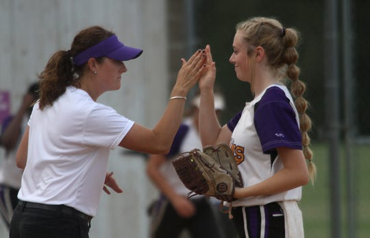 Indianola assistant coach Melisse Jacobson gives sophomore pitcher Kate Kralik a high five.