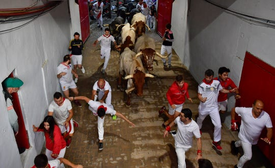 Revellers run next to bulls at the San Fermin Festival, in Pamplona, northern Spain, on Sunday.