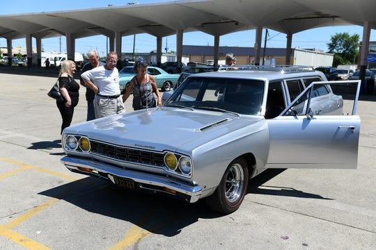 Bill Manes, left, of Chesterfield stands next to Lorraine Colasanti next to the 1968 Plymouth wagon belonging to Lorraine and her husband, Dennis, not shown, at Motors at the Market at Eastern Market in Detroit on Sunday.
