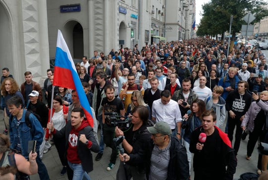 Russian opposition candidate Russian and activist Ilya Yashin, second left, holds a Russian flag during a protest in Moscow, Russia, Sunday.