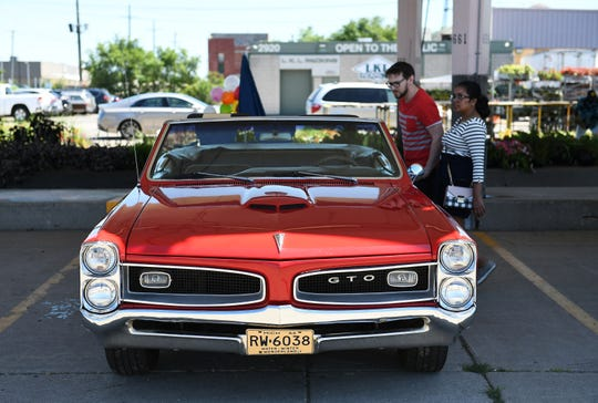 Steve Grzebyk, 33, and his wife, Diluckshi Grzebyk, 31, of Rochester Hills check out a 1966 Pontiac GTO at Motors at the Market at Eastern Market in Detroit on Sunday.