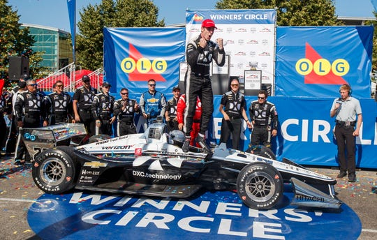 Simon Pagenaud, center, jumps off of his car as he celebrates taking first place at the Honda IndyCar race in Toronto on Sunday.