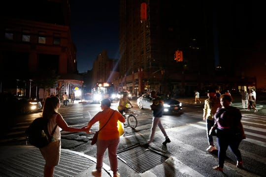 Pedestrians cross a dark street during a power outage, Saturday, July 13, 2019, in New York.