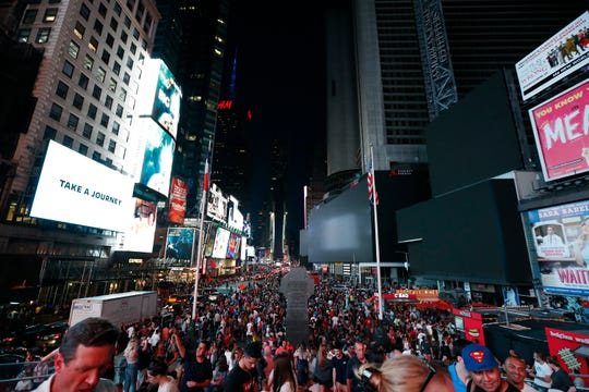 Screens in Times Square are black during a power outage Saturday in New York