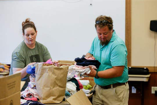 Community members collect donations for the families of the five houses that where destroyed by a fire Friday evening on the 3600 block of Tesla drive, Saturday, July 13, 2019 in Wabash Township. The fire, which also damaged several other homes, is still under investigation