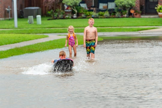 Children playing in water on street dropped by Huricane Barry in Sugar Ridge Subdivision in Youngsville, LA. Hurricane Barry.  Sunday, July 14, 2019.