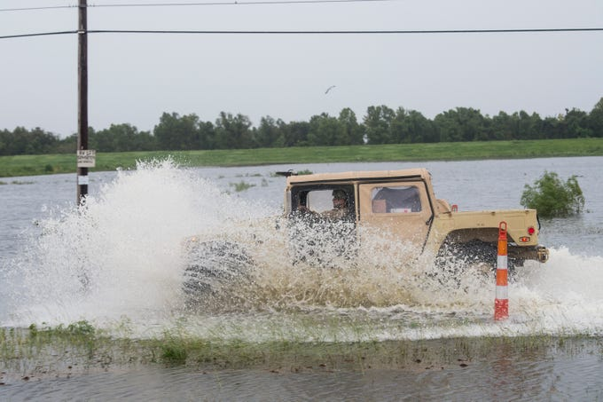 An Army National Guard truck goes through a flooded road on Highway 23 in Plaquemines Parish, La., on Sunday, July 14, 2019.