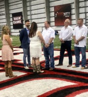 Scott Adams, pastor at Our Savior's Church Midtown Campus in Lafayette, marries Casie Falcon and Garland Young Jr. Saturday morning on the 50-yard line of the UL Lafayette indoor practice field due to Hurricane Barry. Standing with them are maid of honor Ladana Deshotels, father of the bride Anthony Falcon and best man Chris Young.