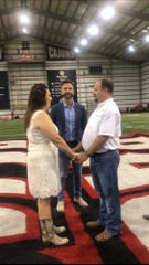 Scott Adams, pastor at Our Savior's Church Midtown Campus in Lafayette, marries Casie Falcon and Garland Young Jr. Saturday morning on the 50-yard line of the UL Lafayette indoor practice field due to Hurricane Barry.