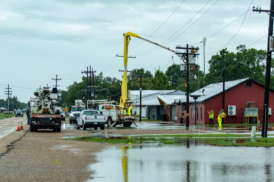 Town of Erath Public Works employees repair electricity poles Sunday morning.