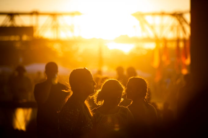 Attendees hang out in the sunset under I-64 Saturday night at the Forecastle Festival. July 12, 2019