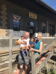 Mason Depot Diner owners Rod and Kathy Hunt, pictured with their grand daughters Phoenix and Raven Rosas in front of the business July 11. The historic former railroad depot was heavily damaged by a fire.