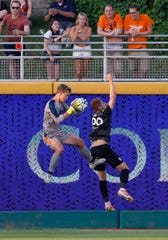 Lansing Ignite goalkeeper Stefan Cleveland, left, takes the ball away from FC Tucson's Jordan Jones, Saturday, July 13, 2019, at Cooley Law School Stadium in Lansing, Mich. The teams played to a 2-2 draw.