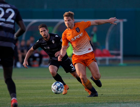 Lansing Ignite's Rafa Mentzingen, right, attacks against FC Tucson's Jose Terron, Saturday, July 13, 2019, at Cooley Law School Stadium in Lansing, Mich. The teams played to a 2-2 draw.
