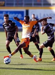 Lansing Ignite's Tumi Moshobane, center, controls the ball against FC Tucson, Saturday, July 13, 2019, at Cooley Law School Stadium in Lansing, Mich. The teams played to a 2-2 draw.