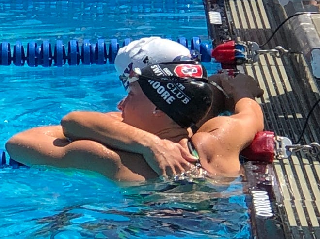 Lexington High School sidekicks and Ohio State Swim Club teammates Sage Moore and Alli McFarland hug after their showdown in the 200 freestyle at the GMAC Championships.