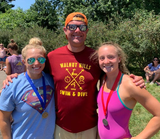 Brock Spurling, coach of overall champ Walnut Hills, flanked by record-setters Alli McFarland (left) of Clear Fork and Sage Moore of Walnut Hills at the GMAC Championships. McFarland and Moore both swam for Spurling's powerhouse Lexington High School program.