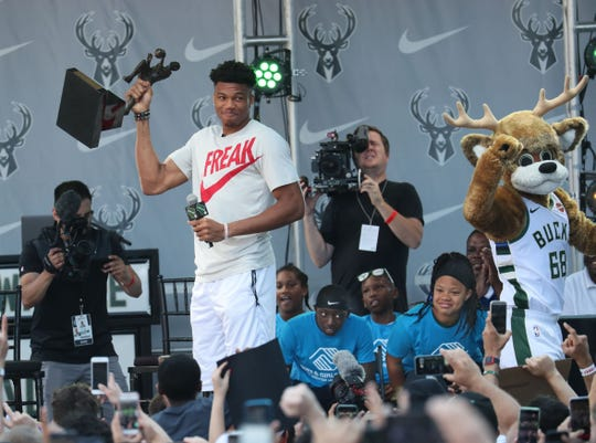 Milwaukee Bucks forward Giannis Antetokounmpo hoists the MVP trophy after being presented with it by youths from local Boys & Girls Club as the crowd cheers during the Giannis MVP Celebration on the plaza at Fiserv Forum on Sunday.