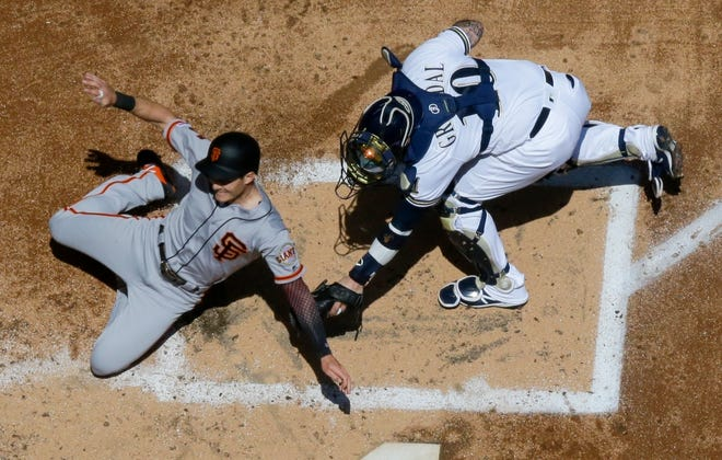 Milwaukee Brewers catcher Yasmani Grandal tags out San Francisco Giants' Mike Yastrzemski at home during the second inning of a baseball game Sunday, July 14, 2019, in Milwaukee. (AP Photo/Morry Gash)