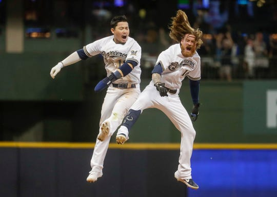 Ben Gamel celebrates with Keston Hiura after hitting a walk-off RBI double in the ninth inning.