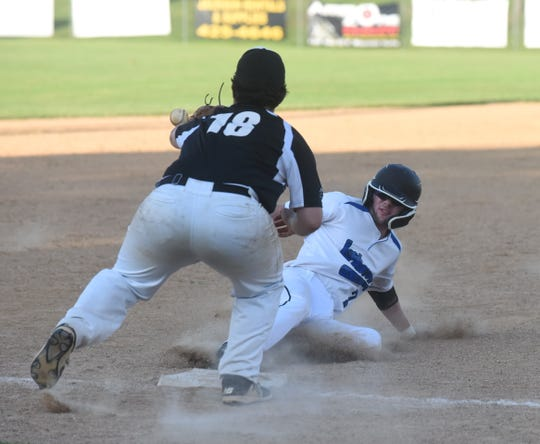 Mountain Home's Charlie Phillips slides safely into third base during Lockeroom's 15-5 victory over Searcy on Saturday night at Cooper Park.