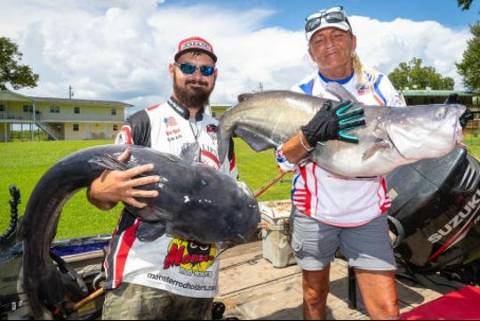 Bryan Folsom, left, shows off his 54.8-pound catfish, and Paula Cathey Smith holds her 30-pounder that helped the team win the Tennessee River Catfish Tournament on Saturday.