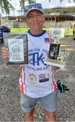 Paula Cathey Smith holds the first-place plaque and trophy her team won in the Tennessee River Catfish Tournament on Saturday.