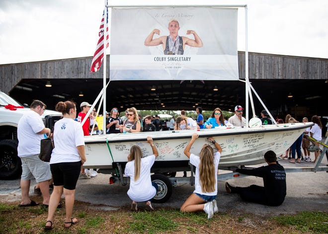 Friends and family members sign a boat with messages of love during a celebration of life for Colby Singletary at the Collier County Fairgrounds on Saturday, July 13, 2019.