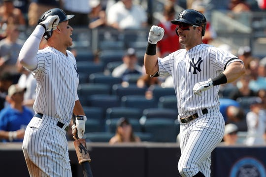 New York Yankees' on-deck batter Aaron Judge, left, celebrates with New York Yankees left fielder Mike Tauchman after Tachman hit solo home run during the seventh inning of a baseball game against the Toronto Blue Jays, Sunday, July 14, 2019, in New York. (AP Photo/Kathy Willens)