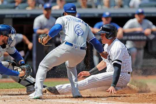 Toronto Blue Jays starting pitcher Marcus Stroman, center, and Blue Jays' catcher Danny Jansen, left, watch as New York Yankees' Gio Urshela, right, slides into home plate trying to score on a wild pitch during the fifth inning of a baseball game, Sunday, July 14, 2019, in New York. (AP Photo/Kathy Willens)
