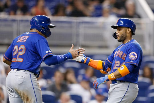 Robinson Cano #24 of the New York Mets celebrates with Dominic Smith #22 after hitting a two-run home run in the eighth inning against the Miami Marlins at Marlins Park on July 13, 2019 in Miami, Florida.