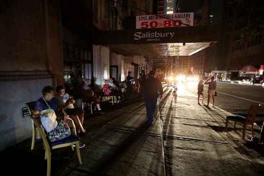 July 13, 2019; New York, NY, USA; People sit outside a midtown hotel after a power outage left large parts of the West Side of Manhattan without power July 13, 2019.