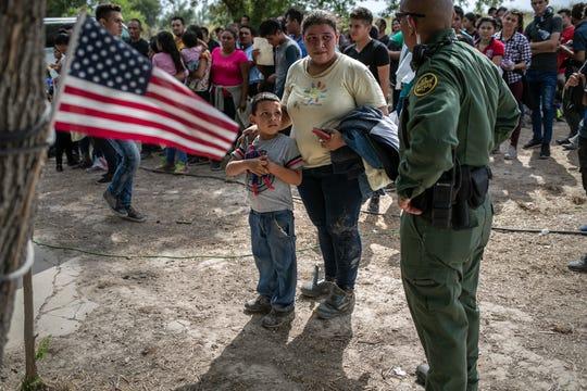 Un agente de la Patrulla Fronteriza hace preguntas a madre e hijo, durante protesta.