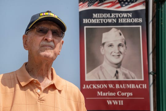 Jack Baumbach, 97, stands next to a banner in Middletown honoring his military career. Baumbach is a WWII vet and Marine who served at Iwo Jima.