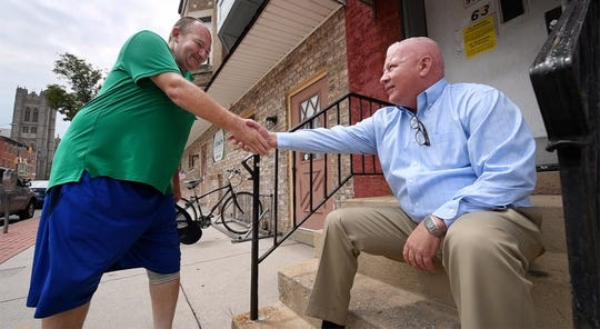Matthew Carey, CEO of LifePath Ministries, shakes hands with a local resident from the stoop in front of the mission on West Market Street.