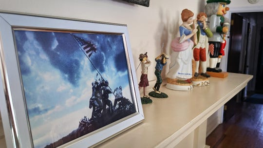 A copy of the iconic flag raising photo at Iwa Jima is displayed on the fireplace mantle next to nick nacks at Jack Baumbach's home.