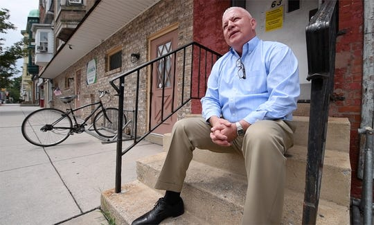 Matthew Carey, CEO of LifePath Ministries, sits on a stoop in front of the mission on West Market Street.