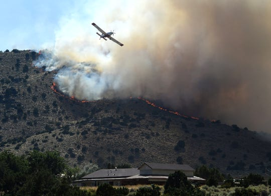 Crews battle the Jasper Fire as it makes its way into Spanish Springs on July 13. Two men have been accused of starting the fire while target shooting.