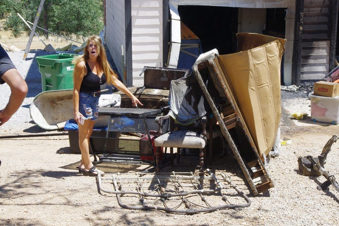 Debbie Reierson looks over furniture that was stacked outside a home she owns on Yuki Yama Lane after the house caught fire Sunday.