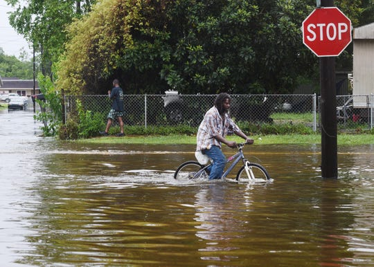 A man tries to bike through the flooding from the rains of storm Barry on LA Hwy 675 in New Iberia, Louisiana, Sunday morning July 14, 2019.