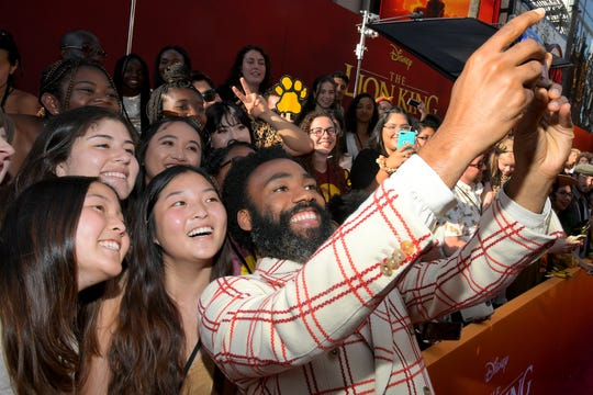 """Donald Glover takes selfies with fans at the world premiere of """"The Lion King"""" on July 9."""