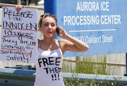 Savannah McNamee, 22, holds a sign protesting ICE raids outside the Denver-area ICE processing facility in Aurora, Colorado, on Sunday, July 14, 2019.