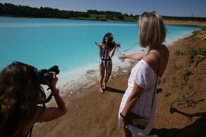 A young woman poses for pictures by an industrial dump site in Siberia whose turquoise lake resembles a tropical paradise.