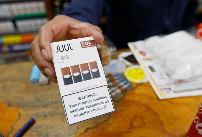 In this Monday, June 17, 2019, file photo, a cashier displays a packet of tobacco-flavored Juul pods at a store in San Francisco.