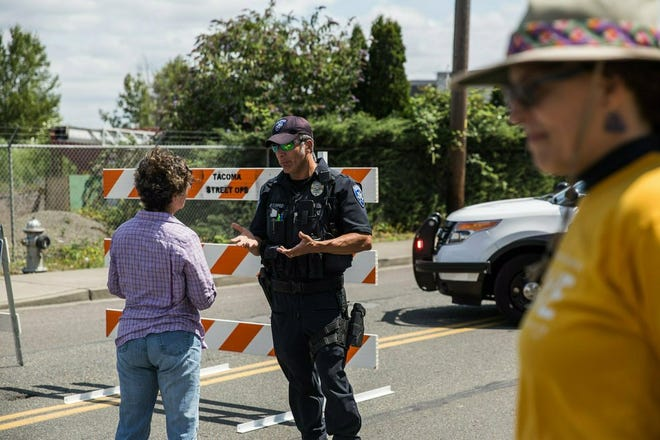 Police Officer Sam Lopez turns away would-be protesters in front of a road block near the Northwest Detention Center, Saturday July 13, 2019 in Tacoma, Wash. A man armed with a rifle threw incendiary devices at an immigration jail in Washington state early Saturday morning, then was found dead after four police officers arrived and opened fire, authorities said.