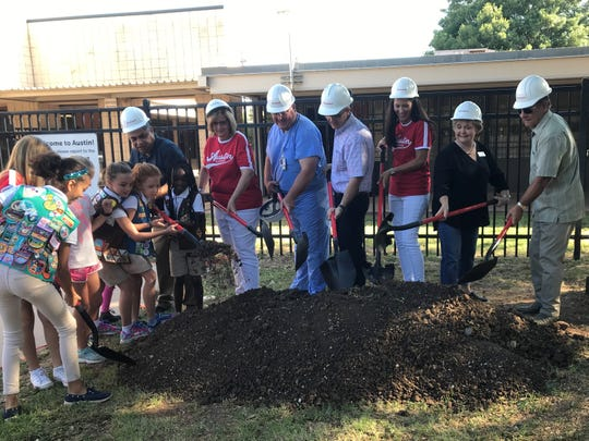 Members of a local Girl Scouts troop help Abilene Independent School District trustee Samuel Garcia, left, throw dirt during a ceremonial groundbreaking at Austin Elementary School on July 15.
