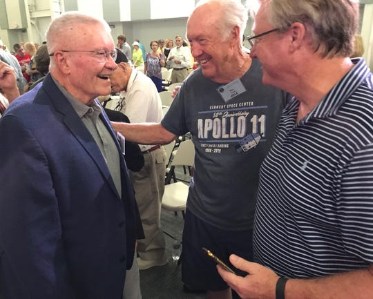 At a reunion for Apollo-era workers at Kennedy Space Center, Apollo 13 astronaut Fred Haise, left, talks with NASA retiree Roy Tharpe, center, and his son, Roy.