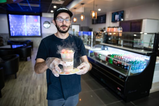 Nick Van Meter, Crescendo Cafe front-end manager, delivers Heaven's Breath and Artist Palette, a liquid nitrogen-infused dish.